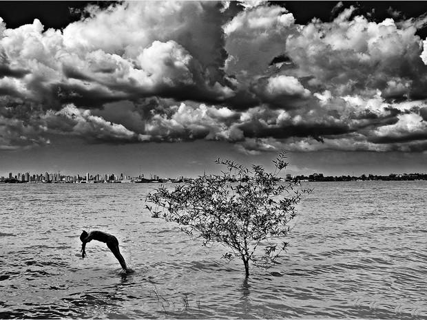 Evna observa a relação do povo paraense com a natureza. Na imagem, criança mergulha no Combu, ao fundo, a capital Belém (Foto: Evna Moura)