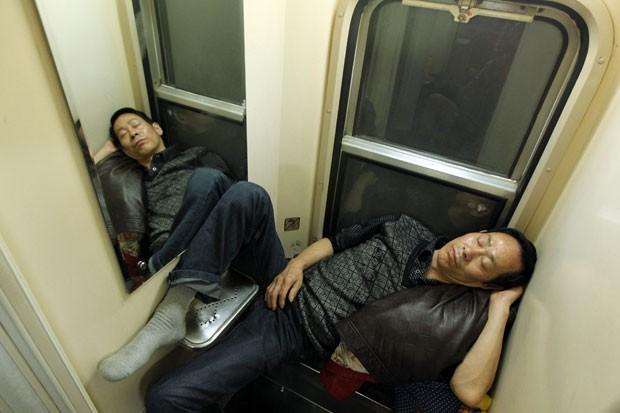 Dupla dorme desajeitada durante viagem de trem entre Guangzhou e Changchun (Foto: AFP)