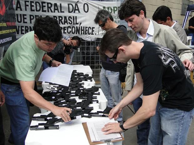 Agentes, escrivães e papiloscopistas fazem fila para entregar as armas (Foto: Pedro Triginelli/G1)