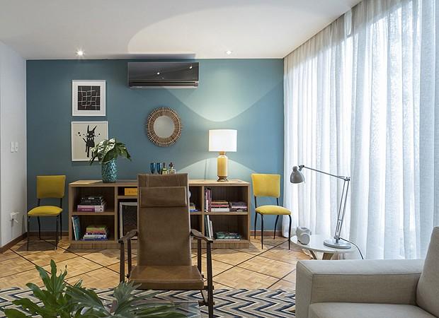 A pedido dos moradores, o arquiteto Robert Robl pintou uma das paredes de azul. O móvel-bar abriga a adega, objetos de decoração e livros (Foto: Thiago Travesso/Divulgação)