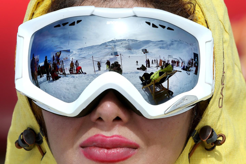 Montanhas congeladas refletidas nos óculos de uma esquiadora, num resort no norte de Teerã (FOTO: REPRODUÇÃO)