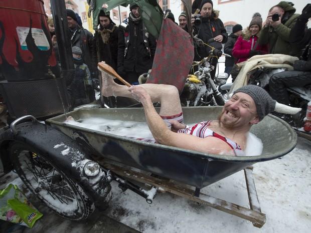 Motociclista improvisou um banho quente no side car de sua moto (Foto: AP Photo/Jens Meyer)