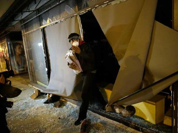 Manifestante saqueia uma loja em Ferguson. (Foto: David Goldman / AP Photo)
