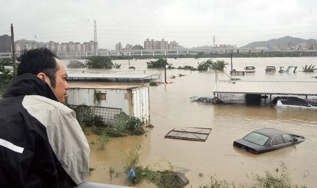 Homem observa carros e estruturas submersas em Tapiei, Taiwan, nesta quinta (2) (Foto: AFP)