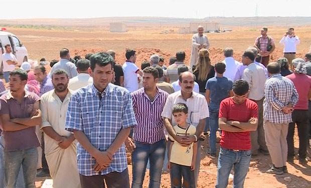 Imagem retirada de vídeo mostra Abdullah Kurdi, que perdeu os dois filhos e a mulher em um naufrágio na Turquia, durante o funeral de sua família em Kobane, na Síria, nesta sexta-feira (4) (Foto: AP)