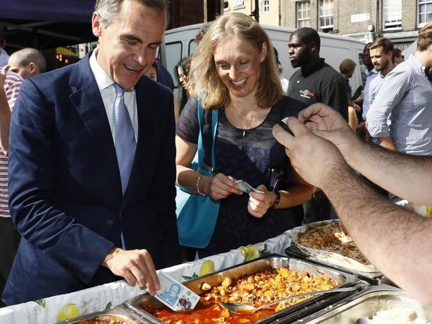 Mark Carney, presidente do Banco da Inglaterra, mergulhou uma nota em uma travessa de comida no mercado de Whitecross Street, em Londres. (Foto: AP)