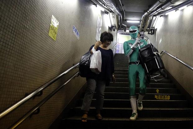 Tadahiro Kanemasu ajudar a descer objetos pelas escadarias (Foto: Yuya Shino/Reuters)