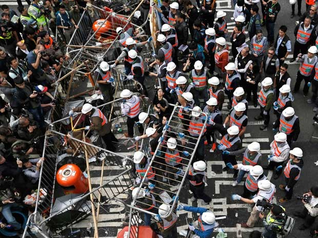 Trabalhadores removem barricadas em uma área bloqueada por manifestantes pró-democracia, perto do edifício sede do governo no distrito financeiro de Hong Kong. (Foto: Athit Perawongmetha / Reuters)