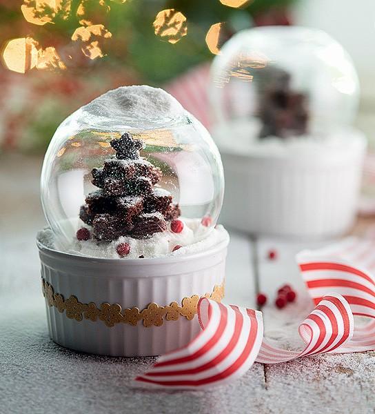 """Dá para acreditar que esse globo de neve é, na verdade, um bolo de chocolate? Para criar esse mimo, use um jogo de cortadores de biscoito em formato de estrela para moldar o doce. Depois, basta colocá-lo em um ramequim coberto por um mini aquário. A """"neve"""" fica por conta do açúcar de confeiteiro. (Foto: Cacá Bratke/Casa e Comida)"""