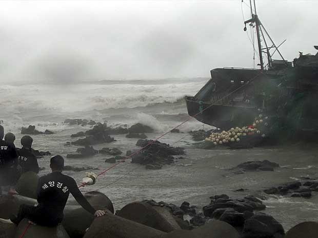 Policiais procuram por integrantes de tripulação de barco de pesca chinês danificado pela força do tufão 'Bolaven' em Seogwipo, região da ilha de Jeju Island, ao sul de Seul, na Coreia do Sul. (Foto: Polícia Marítima de Seogwipo / Reuters)