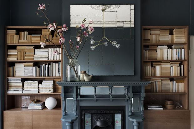 Com paredes escuras e estante de livros casa ganha efeito cool (Foto: Martina Gemmola/Divulgação)