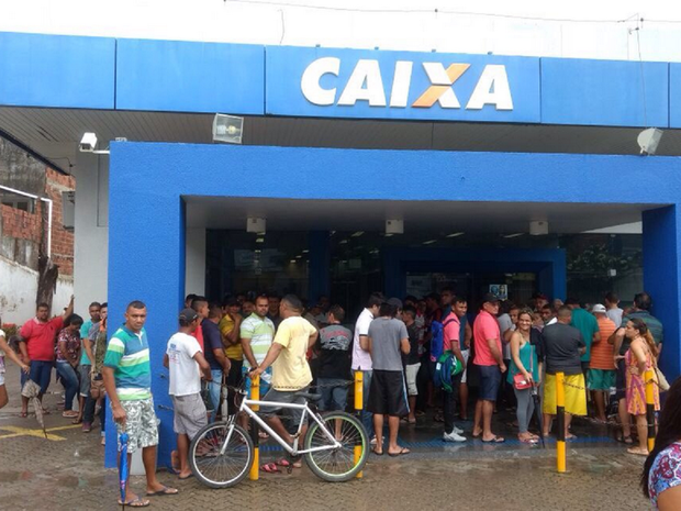 Mesmo com chuva, pessoas formaram longas filas em uma das agências da Caixa Econômica Federal, localizada na Rua Coronel Francisco Pereira, no Bairro Messejana, em Fortaleza (Foto: Valdir Almeida/G1 Ceará)