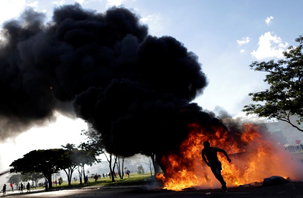 Um manifestante corre perto de uma barricada em chamas durante protesto contra o presidente Michel Temer, em Brasília (Foto: Ueslei Marcelino/Reuters)