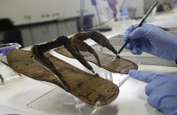 Funcionário higieniza uma sandália de papiro da coleção do faraó Tutancâmon (Foto: AP Photo/Amr Nabil)