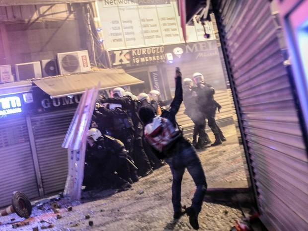 Manifestante joga pedra durante confrontos com a polícia em Kadikoy (Foto: Bulent Kilic/AFP)
