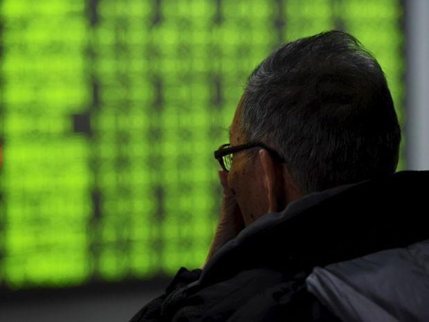 Investidor olha para tela de cotações em um painel em Hangzhou, nesta terça-feira (Foto: Reuters)