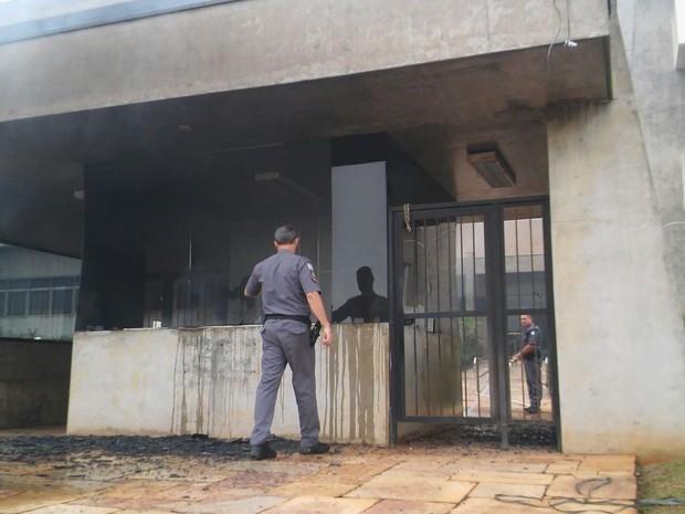 Policial observa guarita da Dedini queimada durante ato de funcionários demitidos em Piracicaba (Foto: Wesley Justino/EPTV)