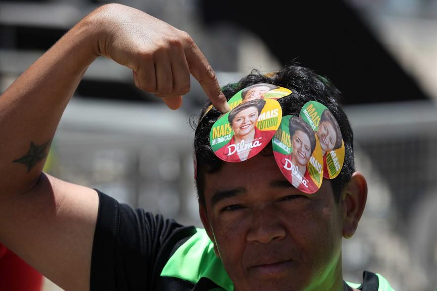 Militante petista aponta para adesivo com foto da presidente Dilma Rousseff, na Esplanada dos Ministérios, em Brasília