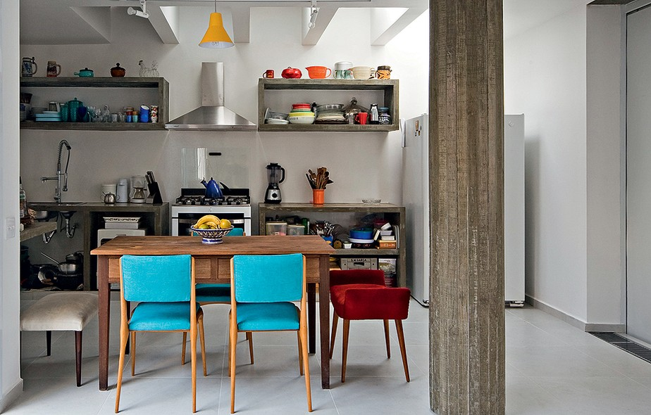 As cadeiras com tecido azul dão cor à cozinha neutra. Na cabeceira, há apenas um banco, no mesmo material, mas vermelho. Projeto do escritório Casa 14 Arquitetura