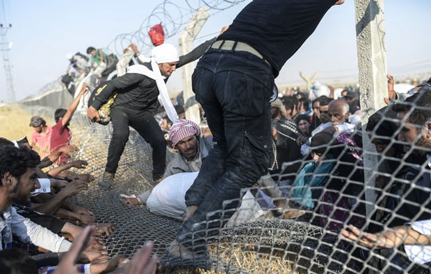 Sírios fugindo do Estado Islâmico atravessam cerca na fronteira com a Turquia neste domingo (14) (Foto: Bulent Kilic/AFP)