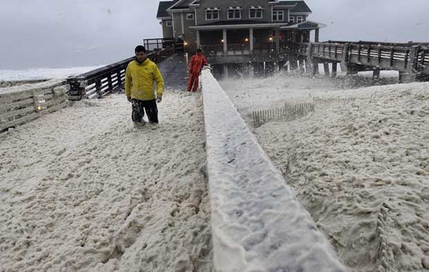 Vento levanta espuma do mar em píer de Nags Head, na Carolina do Norte, neste domingo (28) (Foto: AP)