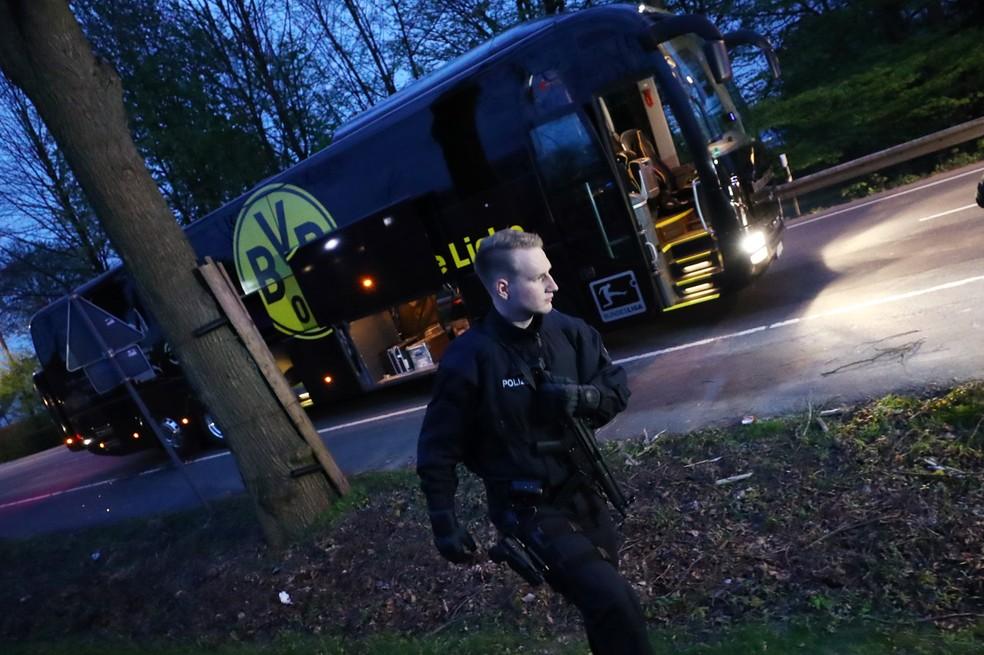 Um policial é visto perto do ônibus do Borussia Dortmund em Dortmund, na Alemanha. O veículo foi danificado após ocorrerem três explosões próximas quando deixava o hotel a caminho do estádio para jogo contra o Monaco pelas quartas-de-final da Champions League. O zagueiro Marc Bartra, de 26 anos, ficou ferido e a partida foi adiada para quarta-feira (12) (Foto: Kai Pfaffenbach/Reuters)