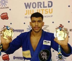 Dino segurando as medalhas de campeão na categoria Super Pesado e na Absoluto (Foto: Divulgação)