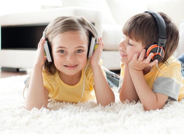 Crianças ouvindo música com fones de ouvido (Foto: Shutterstock)