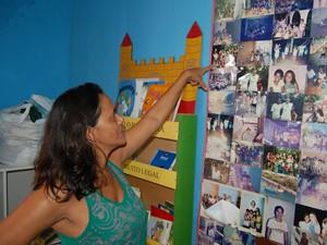 Nilcilene Pontes mostra em painel fotos meninas que moraram na Missão Restauração e moram em outros estados (Foto: André Resende/G1)
