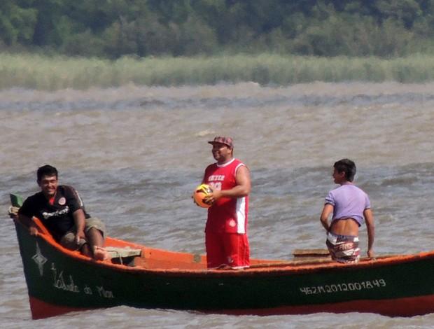 Pescador com brinca com bola após pegá-la no Guaíba (Foto: Tomás Hammes / GLOBOESPORTE.COM)
