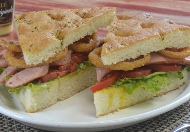 Sanduíche Tedesco, do Zena Café, com salsicha, cebola empanada, alface, tomate, molho de mel e mostarda servido na focaccia (Foto: Divulgação)