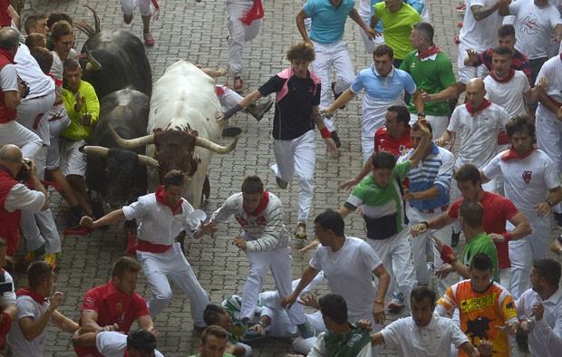 Turistas correm de touro no primeiro dia de corridas do festival de São Firmino em Pamplona nesta terça-feira (7) (Foto: Vincent West/Reuters)