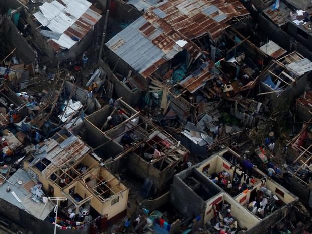 Moradores caminham nesta sexta-feira (7) por entre casas destruídas pela passagem do furacão Matthew em Jeremie, no Haiti (Foto: REUTERS/Carlos Garcia Rawlins)