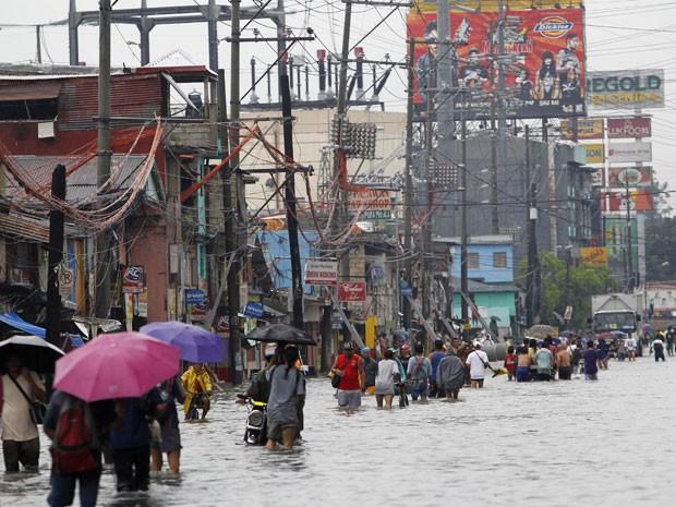 Moradores de Quenzon City, nas Filipinas, caminham por rua inundada neste sábado (15). (Foto: Cheryl Ravelo/Reuters)