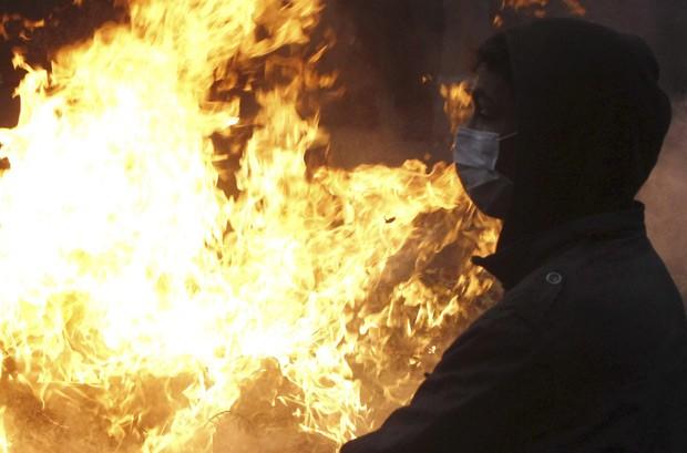 Manifestante em frente a incêndio em ponte próximo à Praça Tahrir, no Cairo, em protestos nesta terça-feira (29) (Foto: Reuters)