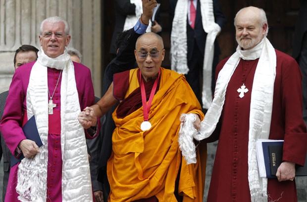 O Dalai Lama, líder espiritual budista do Tibete, recebe o Prêmio Templeton de 2012, por seu trabalho no encorajamento da pesquisa científica e da harmonia entre as religiões, nests segunda-feira (14). Ele está cercado pelo bispo de Londres, Richard Chartres (à direita) e pelo pastor Michael Colclough, da Catedral de St. Paul. O prêmio é de cerca de US$ 1,7, e o Dalai Lama, de 76 anos, já anunciou que ele será doado à ONG Save the Children e a duas entidades dedicadas ao ensino e à pesquisa da ciência e do budismo (Foto: AP)