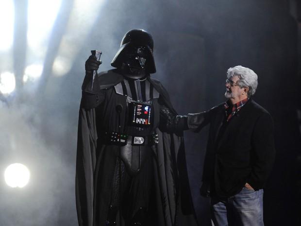 Em foto de outubro de 2011, homem fantasiado de Darth Vader, personagem de 'Guerra nas estrelas' aceita prêmio de 'vilão definitivo' das mãos do seu criador, George Lucas (Foto: AP/Chris Pizzello)