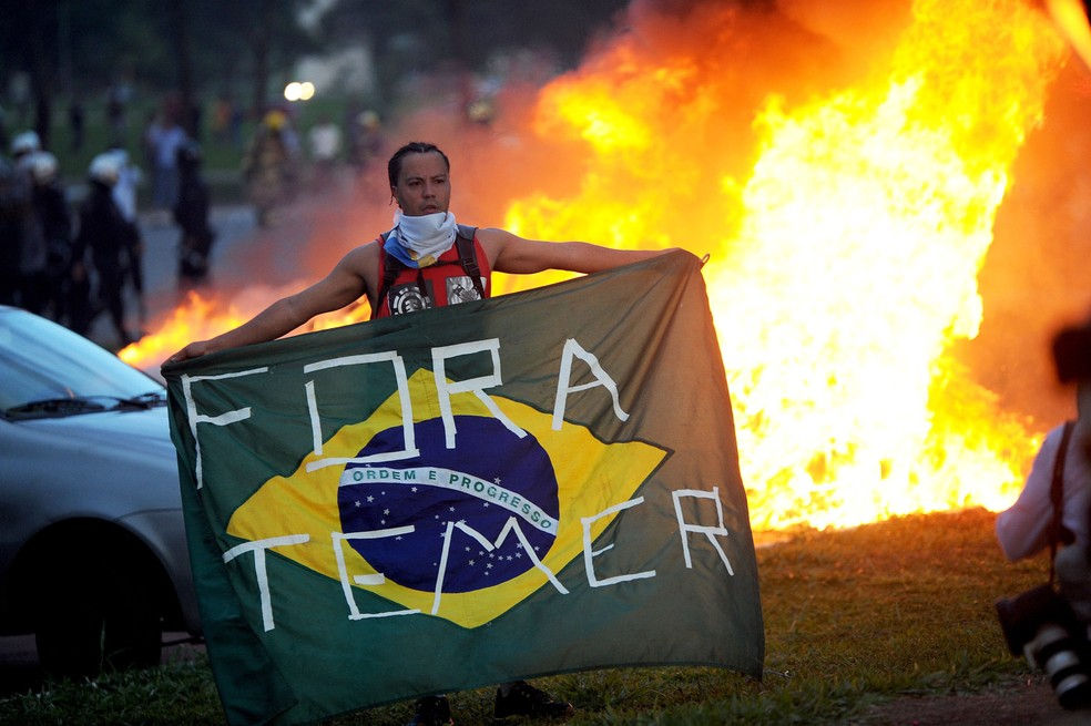 Um estudante exibe uma bandeira do Brasil com a mensagem 'Fora Temer' durante protesto contra a PEC 55, que limita os gastos públicos para os próximos 20 anos, na Esplanada dos Ministérios, em Brasília (Foto: Andressa Anholete/AFP)