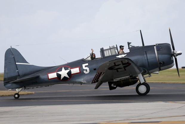 Um dos pilotos acena da janela de um avião de combate SBD Dauntless, da II Guerra Mundial, no New Orleans Lakefront Airport, em Nova Orleans, na quinta (22) (Foto: AP Photo/Gerald Herbert)
