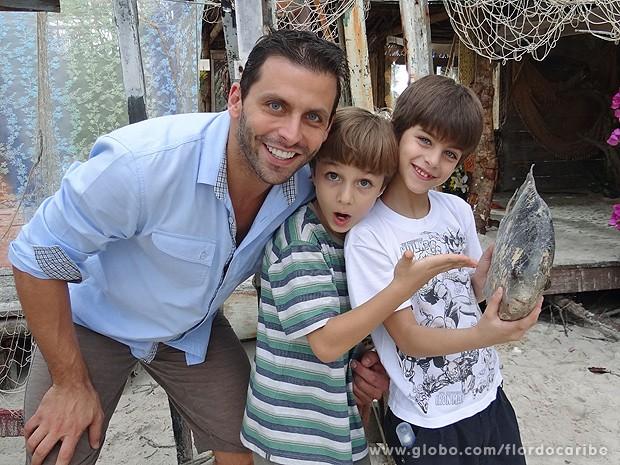 Henri, Vitor e Lucas fazem graça com peixe cenográfico (Foto: Flor do Caribe / TV Globo)