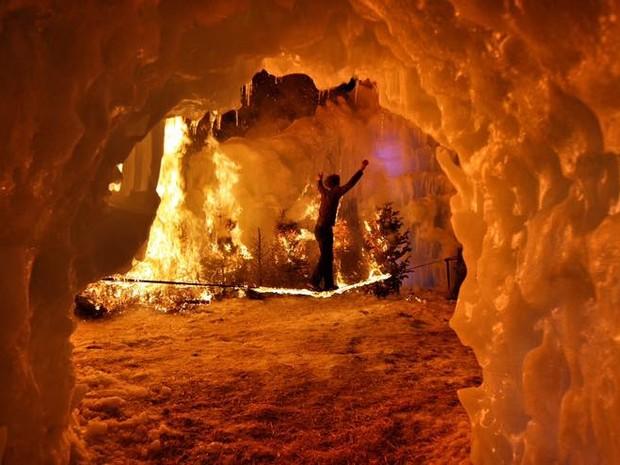 Slackliner se aventura sobre uma corda em chamas, em meio ao castelo de neve de Midway (Foto: Reproduo/Facebook)