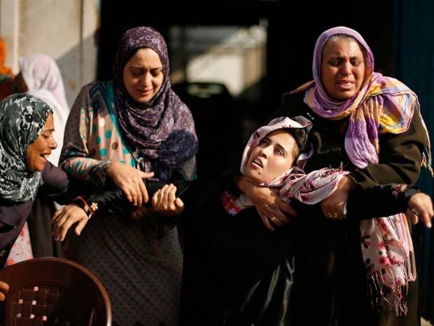 Mulher desmaia e é amparada por amigas depois de saber que sua irmã morreu em ataque aéreo que atingiu uma casa no campo de refugiados de Jabaliya, norte da Faixa de Gaza, neste domingo (3) (Foto: REUTERS/Suhaib Salem)