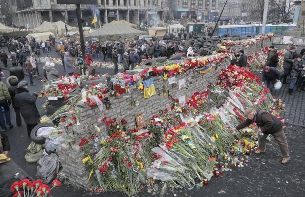 Barricada montada na Praça da Independência, em Kiev, durante os protestos contra o governo da Ucrânia é cercado de flores em homenagem às dezenas de manifestantes que perderam suas vidas nos confrontos com a polícia  (Foto: AP Photo/Efrem Lukatsky)