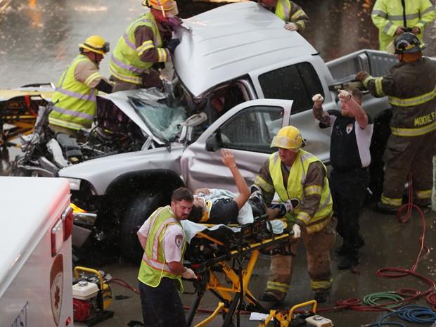 Motorista de caminhão é socorrido após sofrer um acidente causado pelo mau tempo na estrada Interstate 35, em Moore, no Oklahoma, na quarta (6) (Foto: AP Photo/Sue Ogrocki)