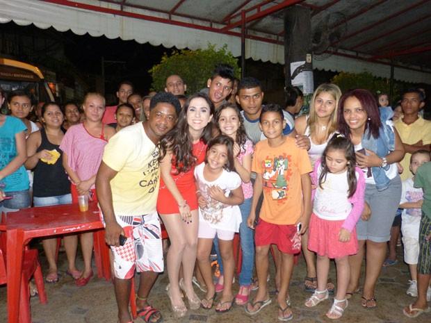 Tatá posa com os moradores (Foto: Amor à Vida/ TV Globo)