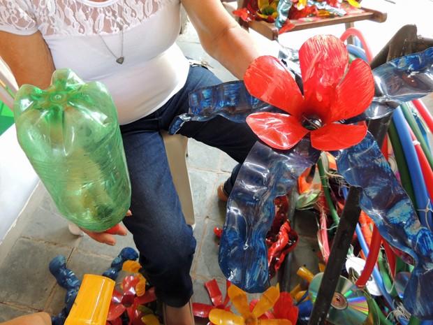Voluntários trabalham com garrafas pet, transformandoa-as em flores (Foto: Katherine Coutinho / G1)