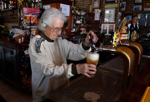 Lil Miles, de 91 anos, serve drink no pub da família em Sydney (Foto: William West/AFP)