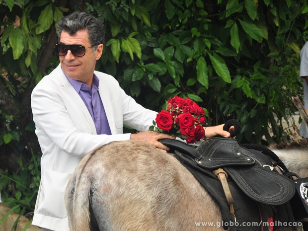 Todo trabalhado no glamour, Paulo Betti tenta subir no animal (Foto: Jacson Vogel / TV Globo)
