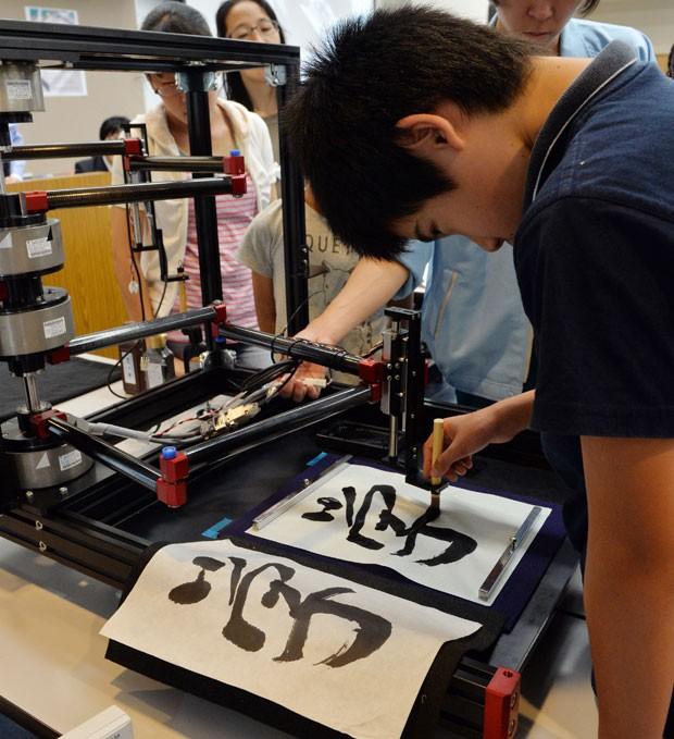 RObô mostra como se escreve e quais os movimentos necessários para escrever (Foto: Yoshikazu Tsuno/AFP)