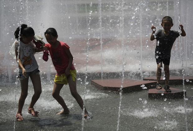 Crianças se refrescam em fonte na cidade chinesa de Xangai nesta segunda-feira (5) (Foto: Eugene Hoshiko/AP)